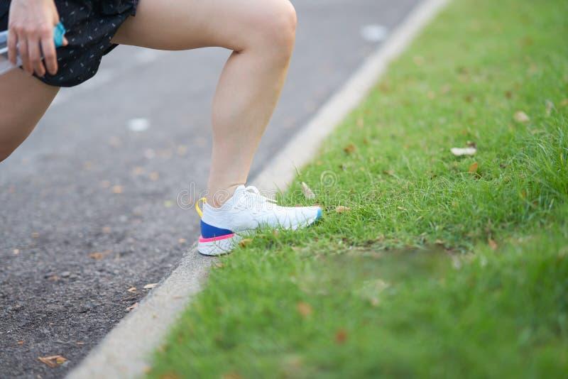 在舒展肌肉的妇女腿在锻炼前在早晨 图库摄影