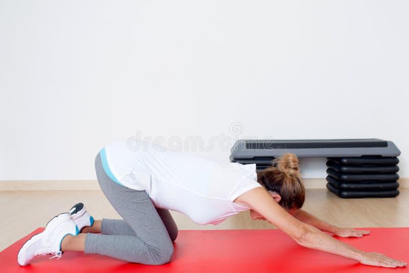 在舒展锻炼期间的年长资深妇女 免版税图库摄影