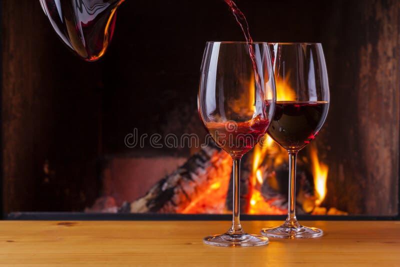 在舒适壁炉的倾吐的红葡萄酒 免版税图库摄影