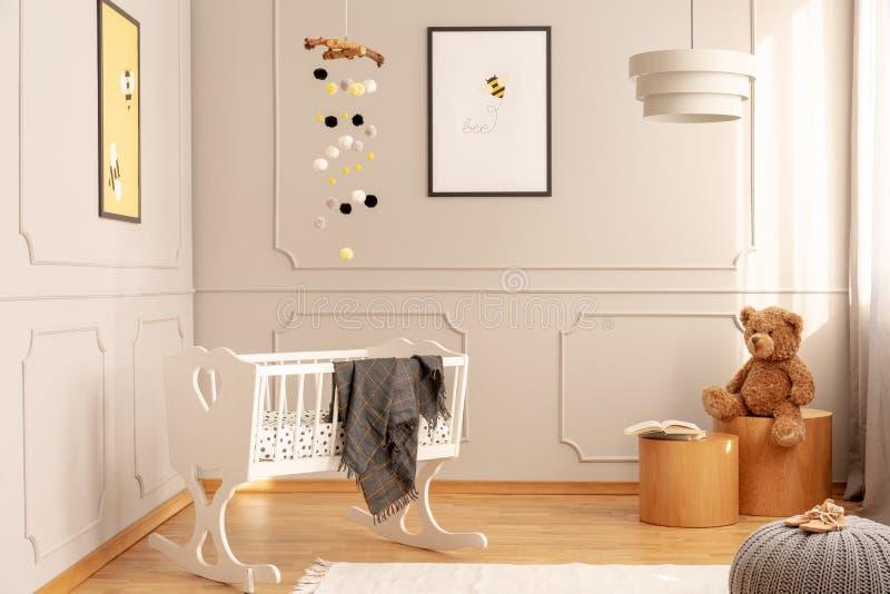 在舒适小孩室内部的白色小儿床与蜂海报、玩具熊和灯 免版税图库摄影