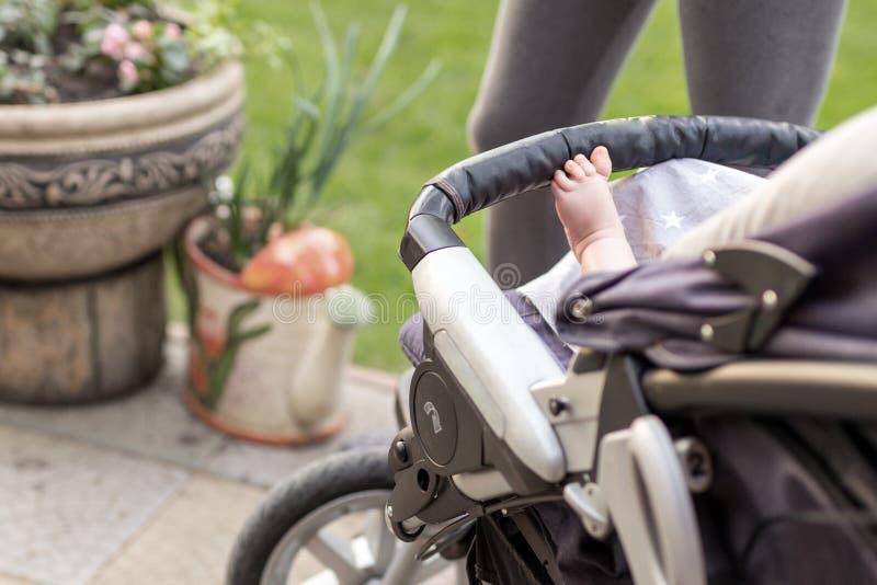 在舒适的婴儿推车的赤足孩子腿 坐在婴儿车的孩子在步行期间户外 背景的运动的母亲 Brigh 库存照片