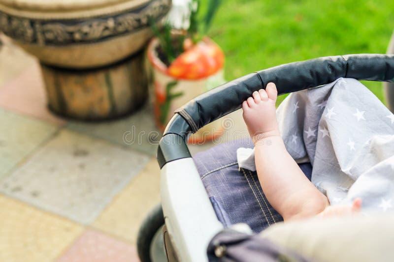 在舒适的婴儿推车的赤足孩子腿 坐在婴儿车的孩子在步行期间户外 明亮的日例证滤网没有夏天使用了向量 库存图片