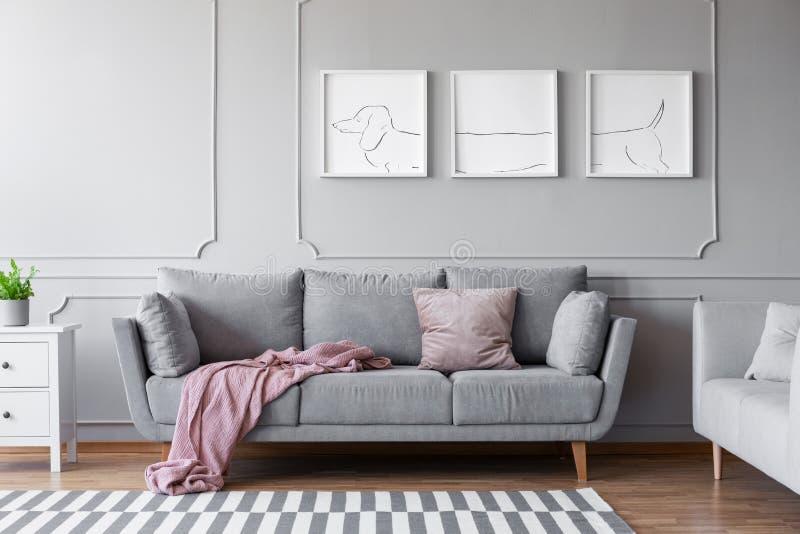 在舒适的灰色长沙发上的狗的海报在与两个沙发的时髦的客厅内部 免版税图库摄影