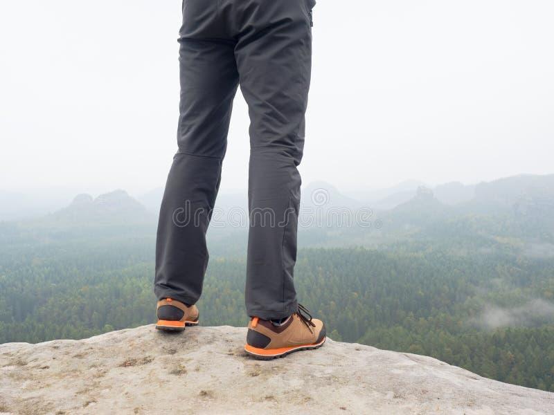 在舒适的迁徙的起动的远足者腿在岩石 供以人员在轻的室外长裤,皮鞋的腿 免版税图库摄影
