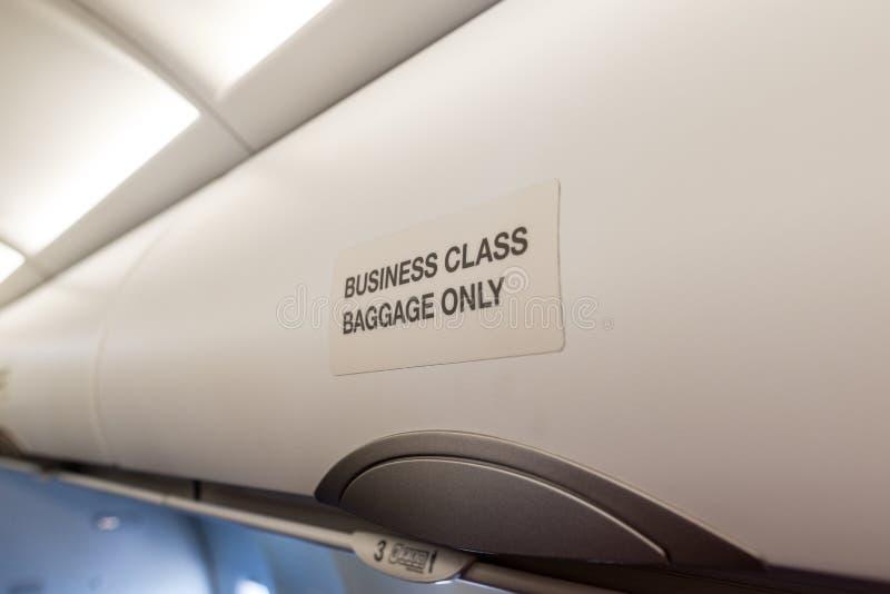 在航空器业务分类的行李架子 在现代企业喷气机的豪华内部 免版税库存照片