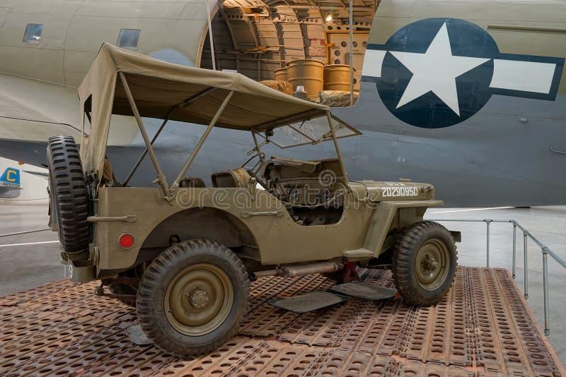 在航空器前面的军用吉普 免版税库存照片