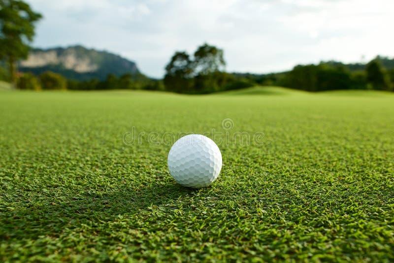 在航路的白色高尔夫球有在coun的绿色背景 图库摄影
