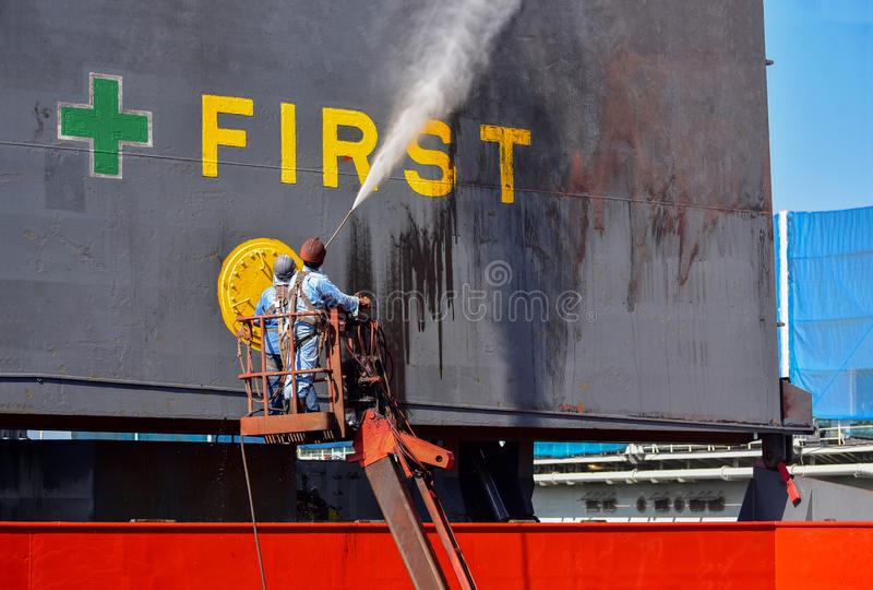 在舱口盖盖子船和清洗的洗涤物货船在浮船坞由高压喷水 图库摄影
