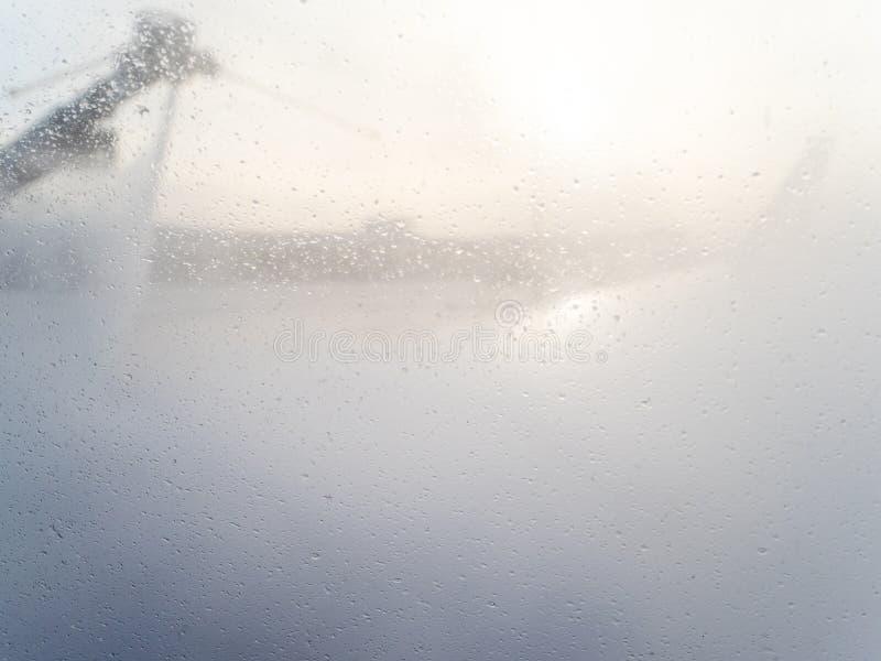 在舷窗的液体下落在除冰期间 免版税库存照片