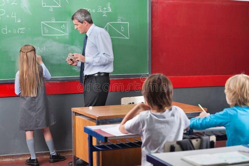 在船上解决数学的小女小学生 免版税库存图片
