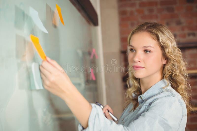 在船上黏附笔记的美丽的女实业家在办公室 库存图片