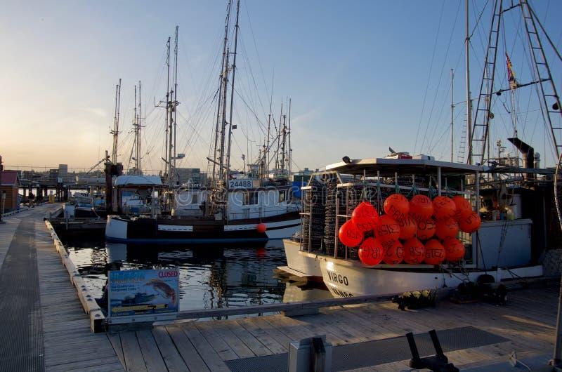 在船坞,一的商业捕鱼业小船与附属的几个明亮的红色浮游物 免版税库存照片