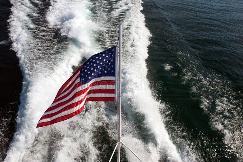 在船苏醒的背景的美国旗子 库存图片
