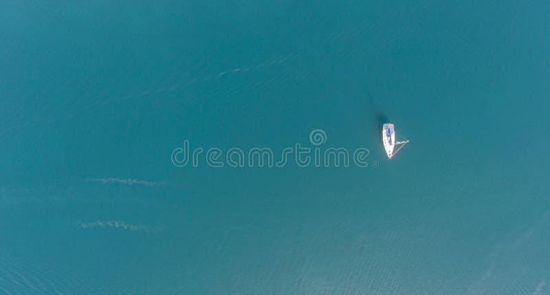 在船锚的一条孤立航行游艇 鸟瞰图 免版税库存照片