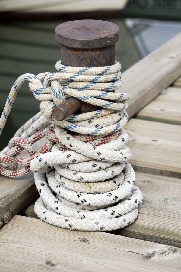 在船系船柱附近被打结的绳索 免版税图库摄影
