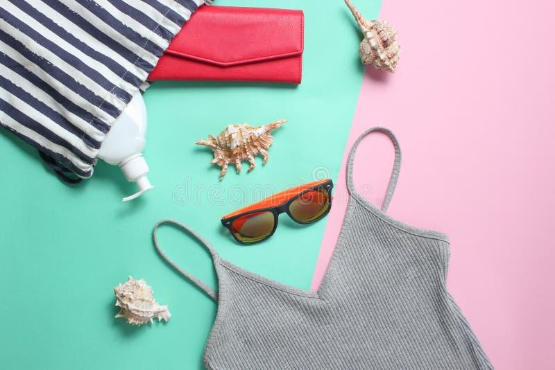 在色的淡色背景的海滩辅助部件 海滩袋子,T恤杉,太阳镜,钱包,sunblock,海扇壳 顶视图 免版税库存图片