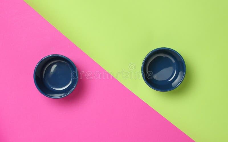 在色的背景的两个蓝色搪瓷碗 顶视图 免版税库存照片
