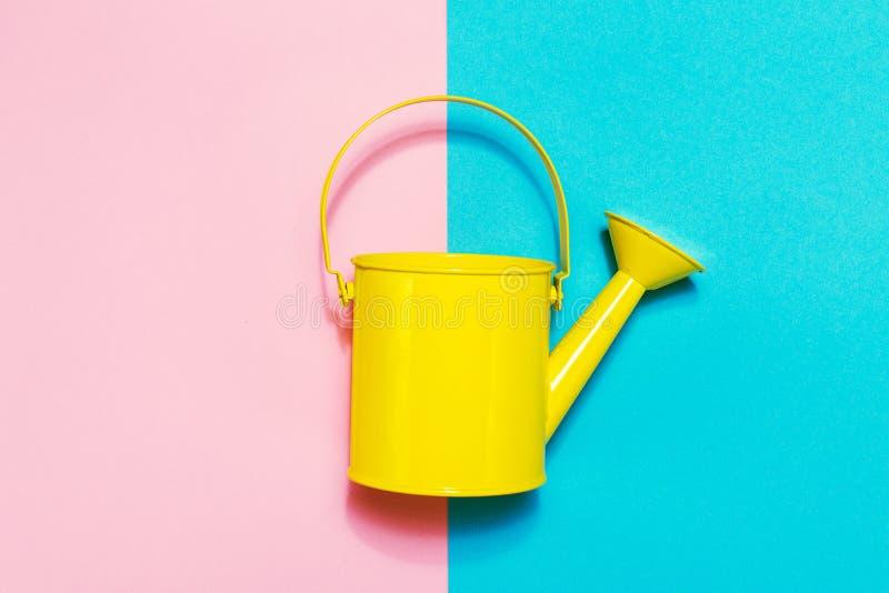 在色的背景的五颜六色的喷壶 平的位置 Minimalis 免版税库存照片