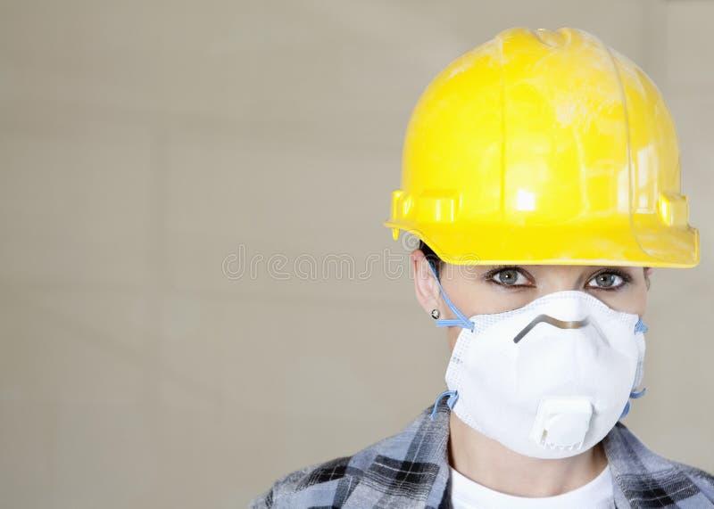 在色的背景的女工佩带的防尘面具画象和安全帽 免版税库存照片