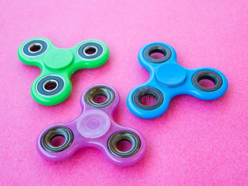 在色的背景的普遍的五颜六色的坐立不安锭床工人玩具 库存图片
