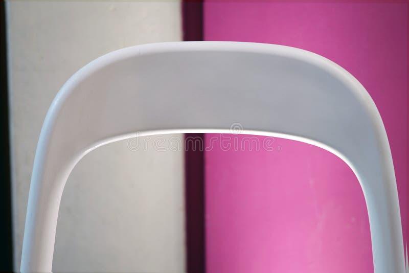 在色的背景的白色椅子 库存图片