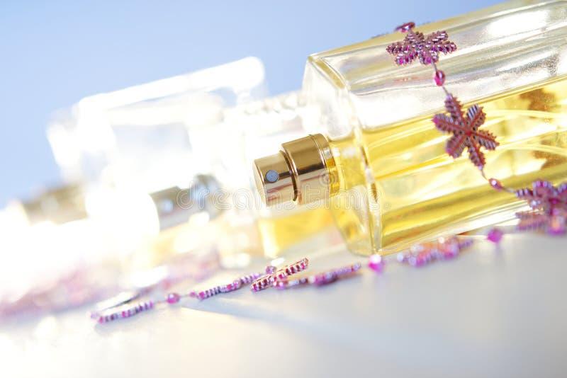 在色的背景的透明香水瓶 秀丽产业 免版税库存图片