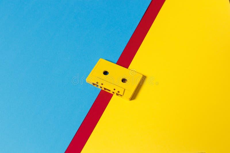 在色的背景,等轴测图的黄色卡型盒式录音机磁带 减速火箭的技术的创造性的概念 免版税库存图片