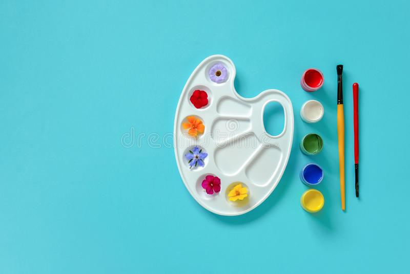 在艺术性的调色板,刷子,在蓝色背景,拷贝空间的树胶水彩画颜料的五颜六色的花 创造性的概念夏天颜色或 免版税库存图片