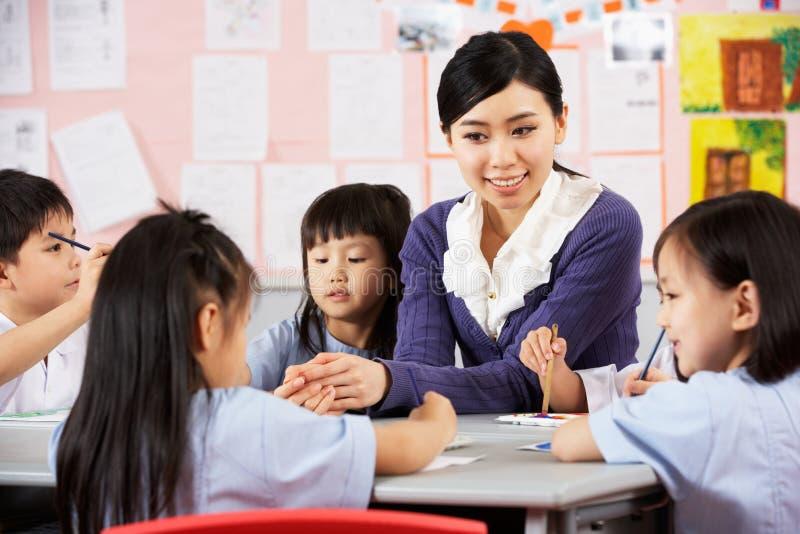在艺术课期间的教师帮助的学员 图库摄影