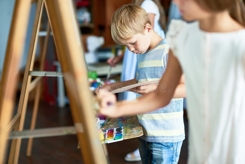 在艺术课的小男孩绘画 免版税库存图片