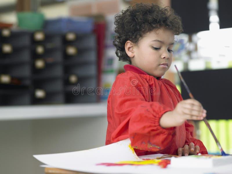 在艺术课的男孩绘画 免版税库存照片
