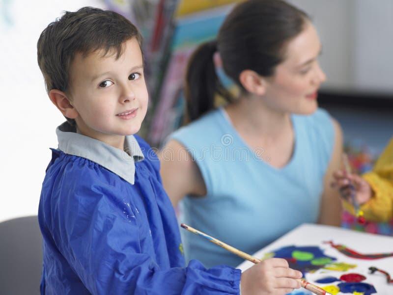 在艺术课的逗人喜爱的男孩绘画 免版税库存照片