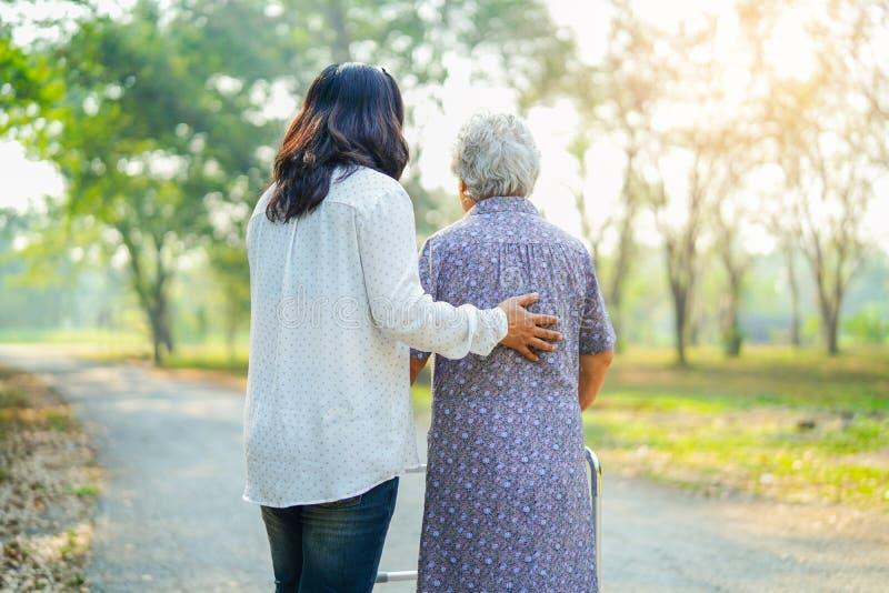 在节日快乐时帮助并且关心亚裔资深或年长老妇人妇女用途步行者以强的健康,当走在公园 免版税库存照片