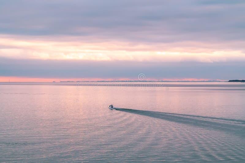 在芬兰海湾的巡逻艇在日落 免版税库存图片