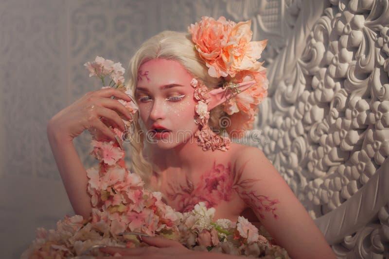 在花中的可爱的她矮子 创造性的构成和bodyart 库存图片