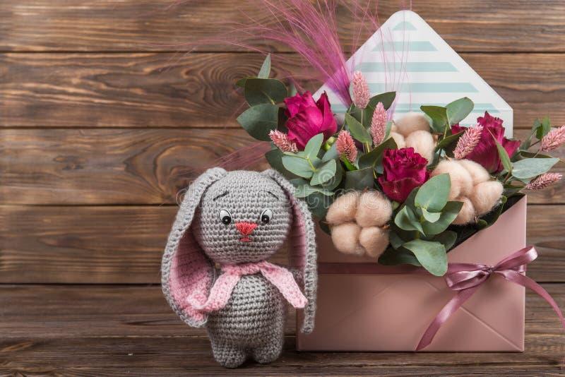 在花信封的安排在软的桃红色的与棉花,钩针编织玩具野兔 百花香 免版税库存照片