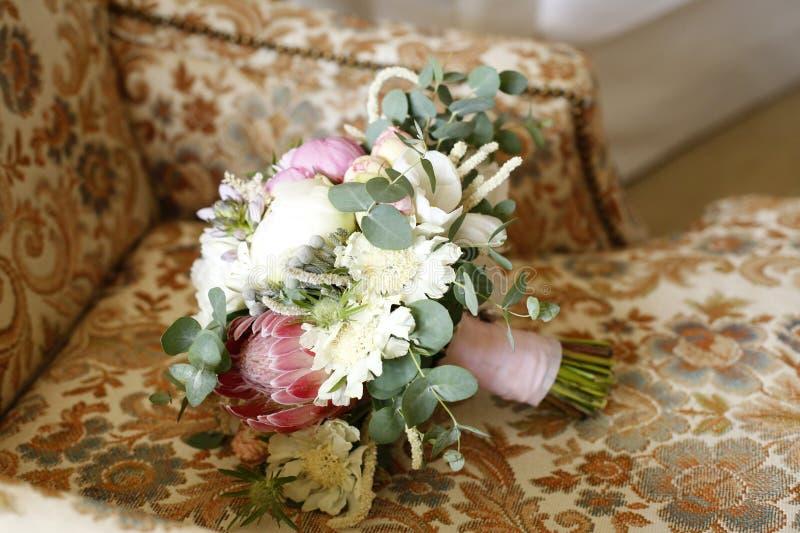 在花卉椅子的美丽的新娘花束 库存图片