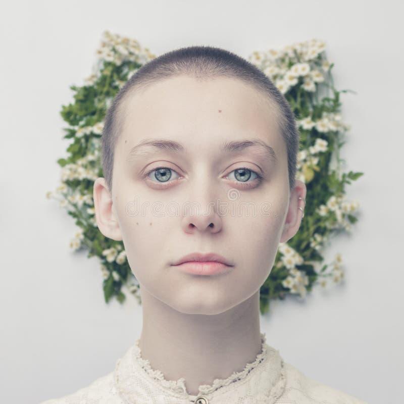 在花卉背景的美丽的秃顶的女孩 免版税库存图片