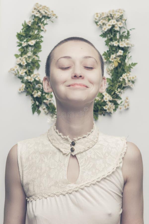 在花卉背景的美丽的秃顶的女孩 库存照片