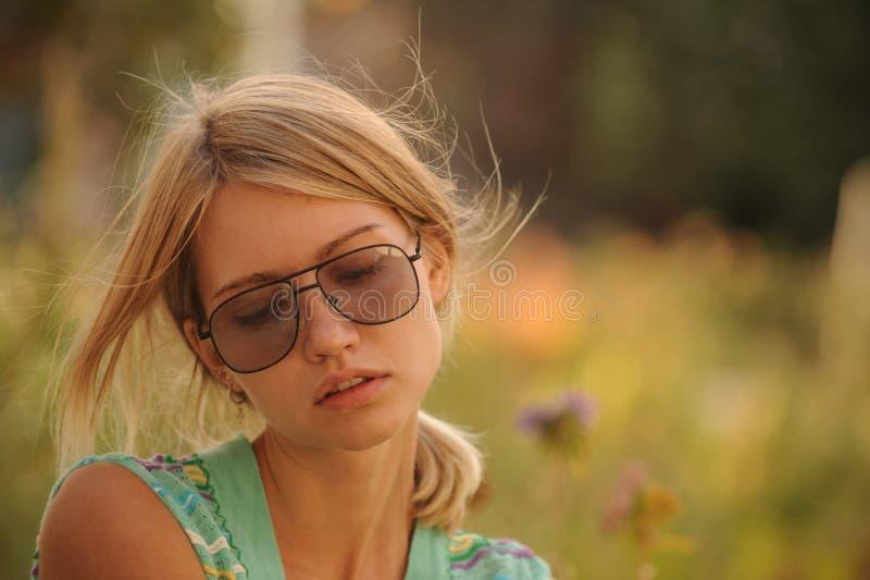 在花圃的美丽的女孩浇灌的花 一位好主妇的概念在她的房子里 库存图片