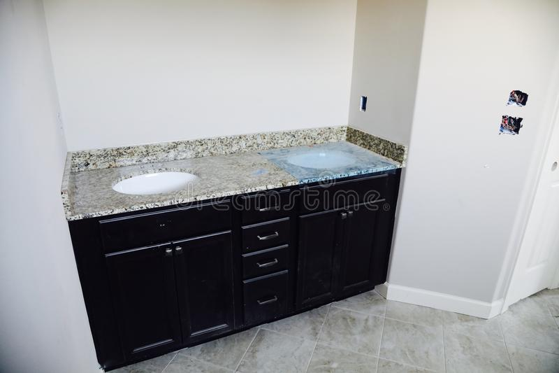 在花岗岩的卫生间水槽安装 库存图片