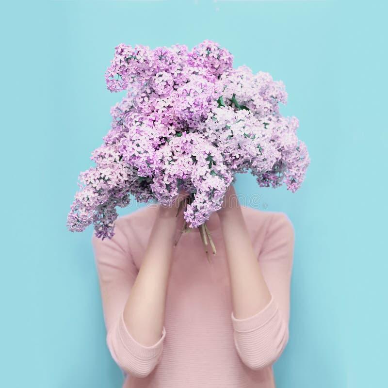 在花束淡紫色花的妇女掩藏的头在五颜六色的蓝色 免版税库存照片