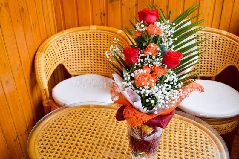 在花束的红色和黄色玫瑰与在桌上的被散置的白花 库存照片