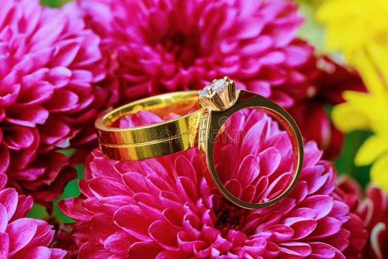 在花束的结婚戒指在桃红色花 免版税库存照片