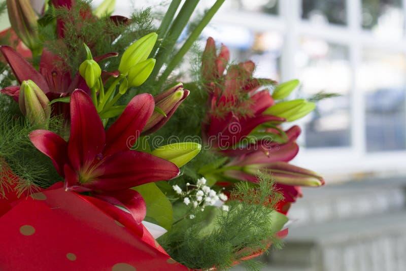在花束的美丽的红色百合特写镜头 美丽的百合花束与春天的在花束开花 精美白百合 免版税库存图片