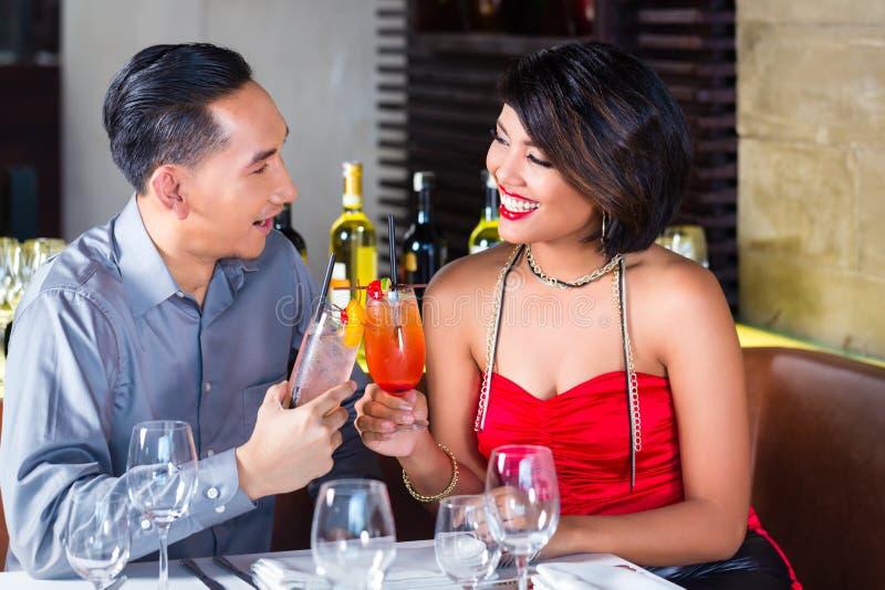 在花梢酒吧的夫妇饮用的鸡尾酒 库存图片