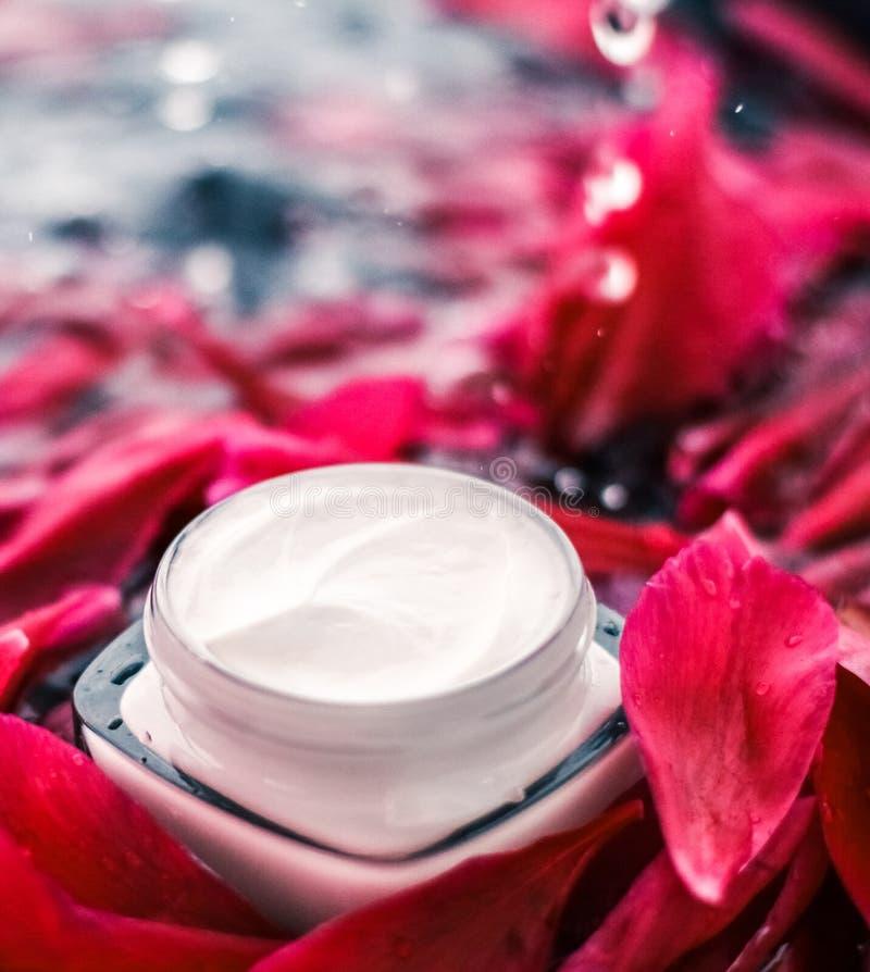 在花瓣和水背景,皮肤的自然科学的敏感skincare润肤霜奶油 库存图片