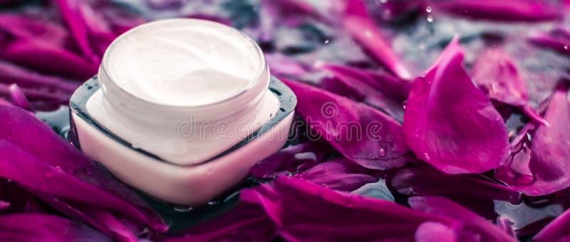 在花瓣和水背景,皮肤的自然科学的敏感skincare润肤霜奶油 免版税库存图片