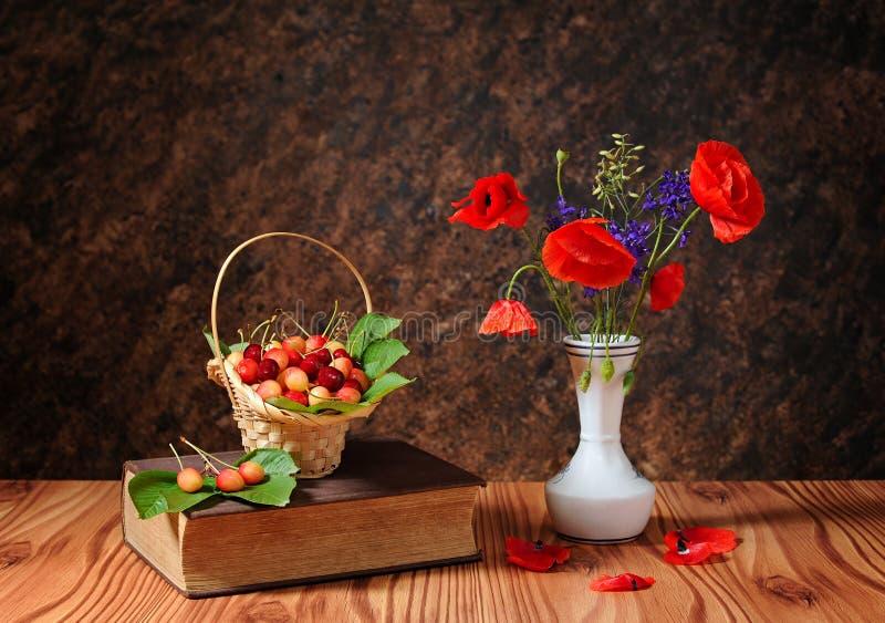在花瓶和樱桃的红色鸦片 图库摄影