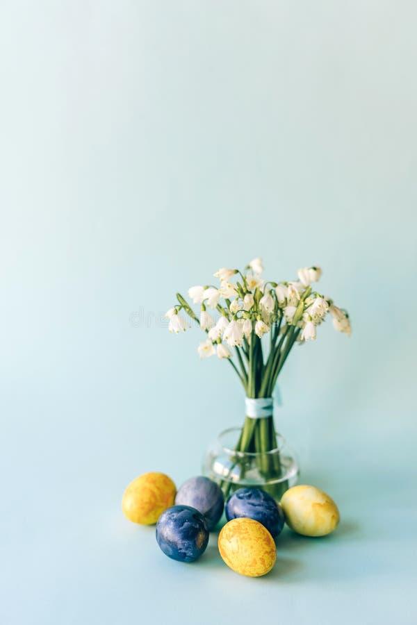 在花瓶和装饰的复活节彩蛋的Snowdrops 免版税库存照片